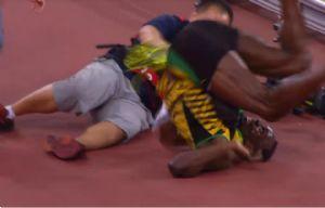Bolt es derribado por el cámara cuando festejaba el oro.