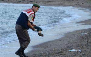 Un guardia turco levanta el cuerpo del menor que apareció en una playa.