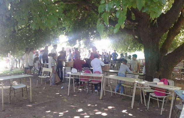 Los niños toman clases bajo el árbol.