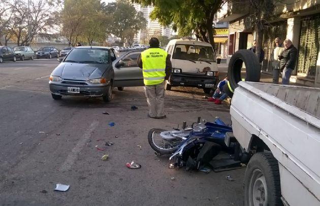 La moto quedó entre dos vehículos y sus ocupantes en la vereda.