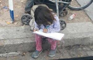 La nena que hace los deberes en plena calle.