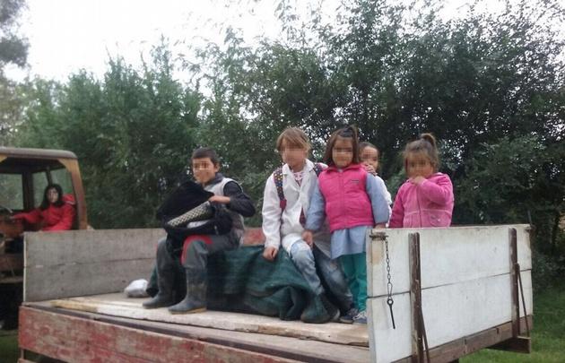 Los niños son trasladados a la escuela en tractor.