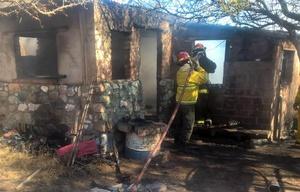 Bomberos apagan el incendio en la casa de la víctima. Fue el fin de semana.
