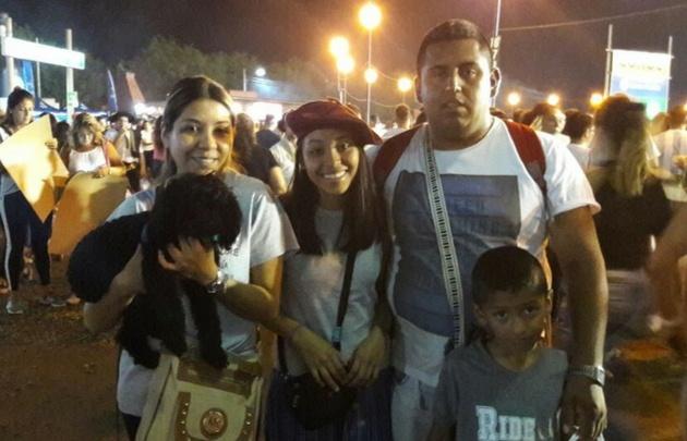 Una familia posa junto a su perro en el festival.